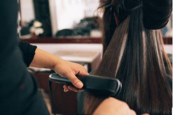alisar el pelo con la plancha en la peluqueria